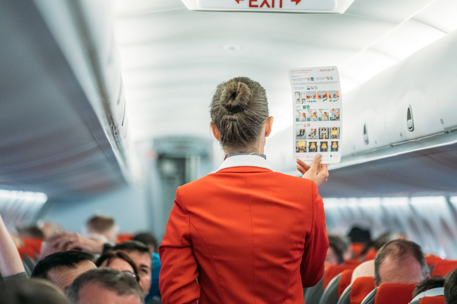 flight attendant holding up safety card in front of passengers