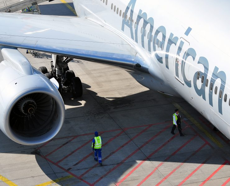 american airlines aircraft on the tarmac with ground staff stood under wing