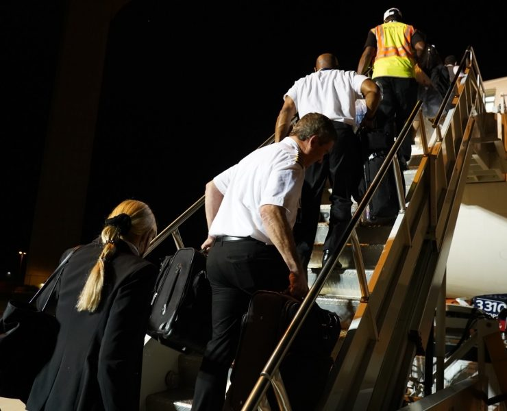 delta air lines employees walk up steps to plane
